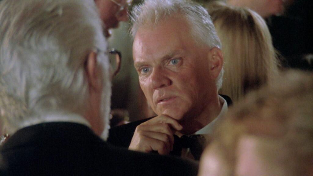 Malcolm McDowell, der sich in The Player selbst spielt, greift sich nachdenklich ans Kinn.