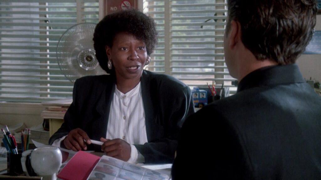 Susan Avery (Whoopi Goldberg) befragt den unter Mordverdacht stehenden Griffin Mill (Tim Robbins) in der örtlichen Polizeistation. In ihren Händen hält sie einen Kugelschreiber.