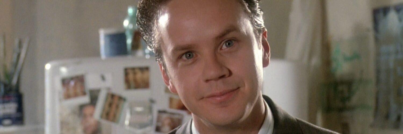 Griffin Mill (Tim Robbins), blickt direkt in die Kamera. Er trägt einen Anzug, im Hintergrund ist ein Kühlschrank mit vielen Magneten zu sehen.