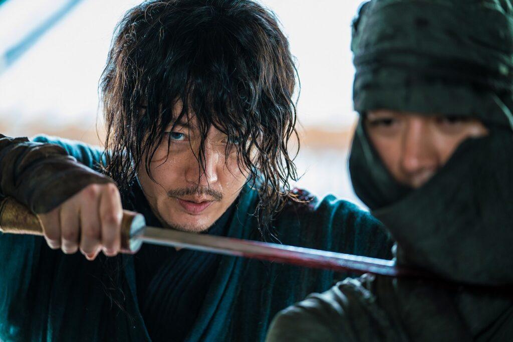 Jang Hyeok schleicht sich mit blutbeschmierter Klinge an einen feindlichen Qing-Soldaten heran - The Swordsman.