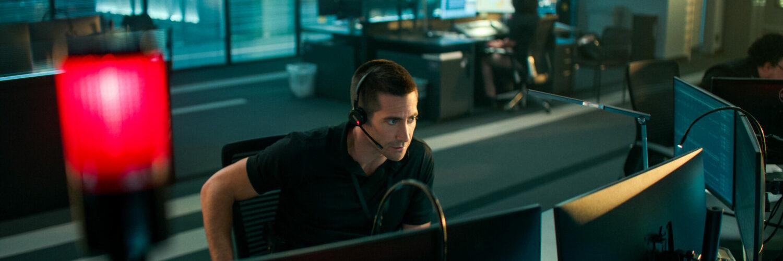 Jake Gyllenhaal in der Rettungszentrale vor zwei Flachbildschirmen mit Headset. Im Vordergrund sieht man eine rote Lampe leuchten