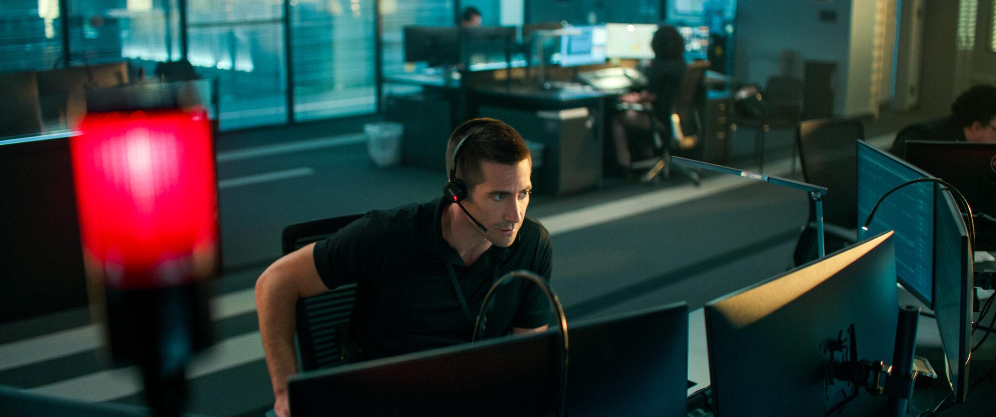 Jake Gyllenhaal mit Headset in einem Büro hinter drei Bildschirmen. Er trägt ein schwarzes Shirt. Vorn im Bild sieht man eine rote Leuchte.
