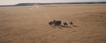 Eine Kutsche fährt über weites Land begleitet von mehreren Reitern.