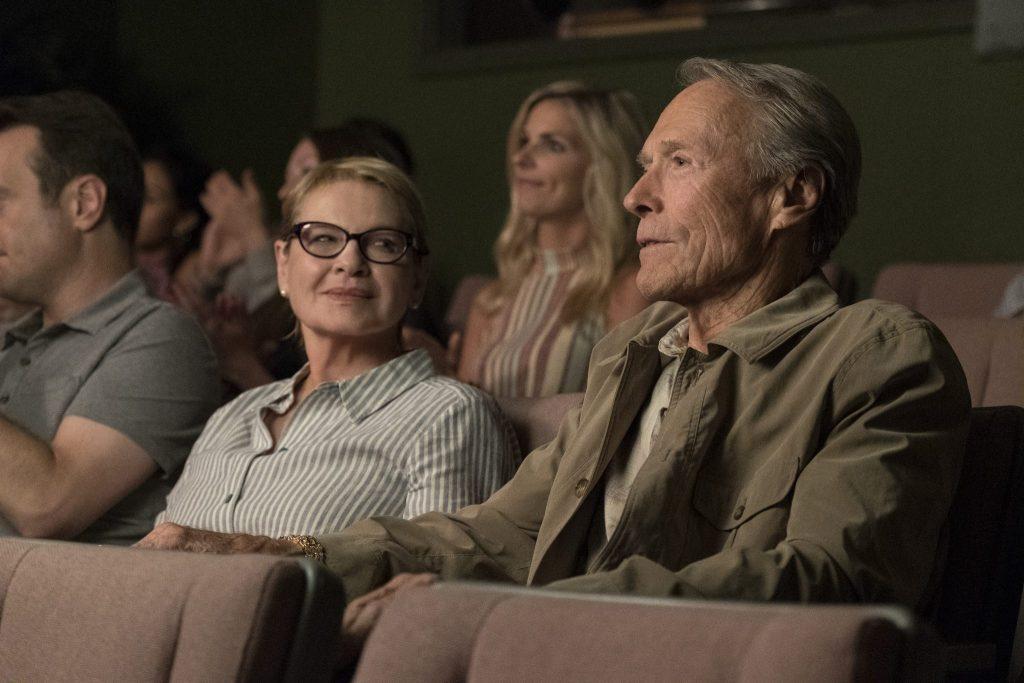 Earl Stone sitzt rechts im Bild, seine Ex-Frau Mary links, also an seiner rechten Seite. Sie befinden sich mit mehrerenn anderen Gästen in einer Art Kinosaal und kommen ins Gespräch.
