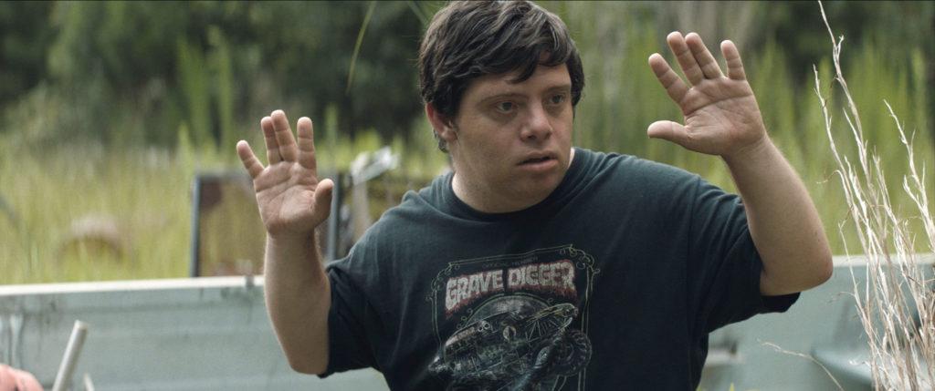 Zak (Zack Gottsagen) hält die Hände in die Luft