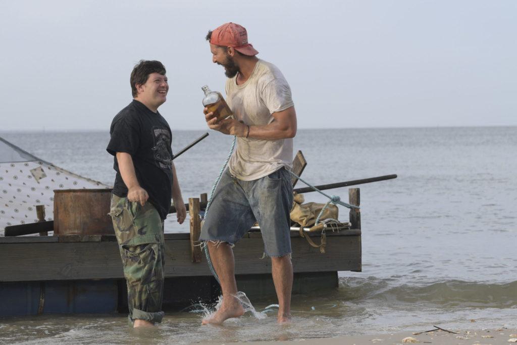 Terry (Rechts) und Zak (Links) stehen lachend vor ihrem Floß am Ufer