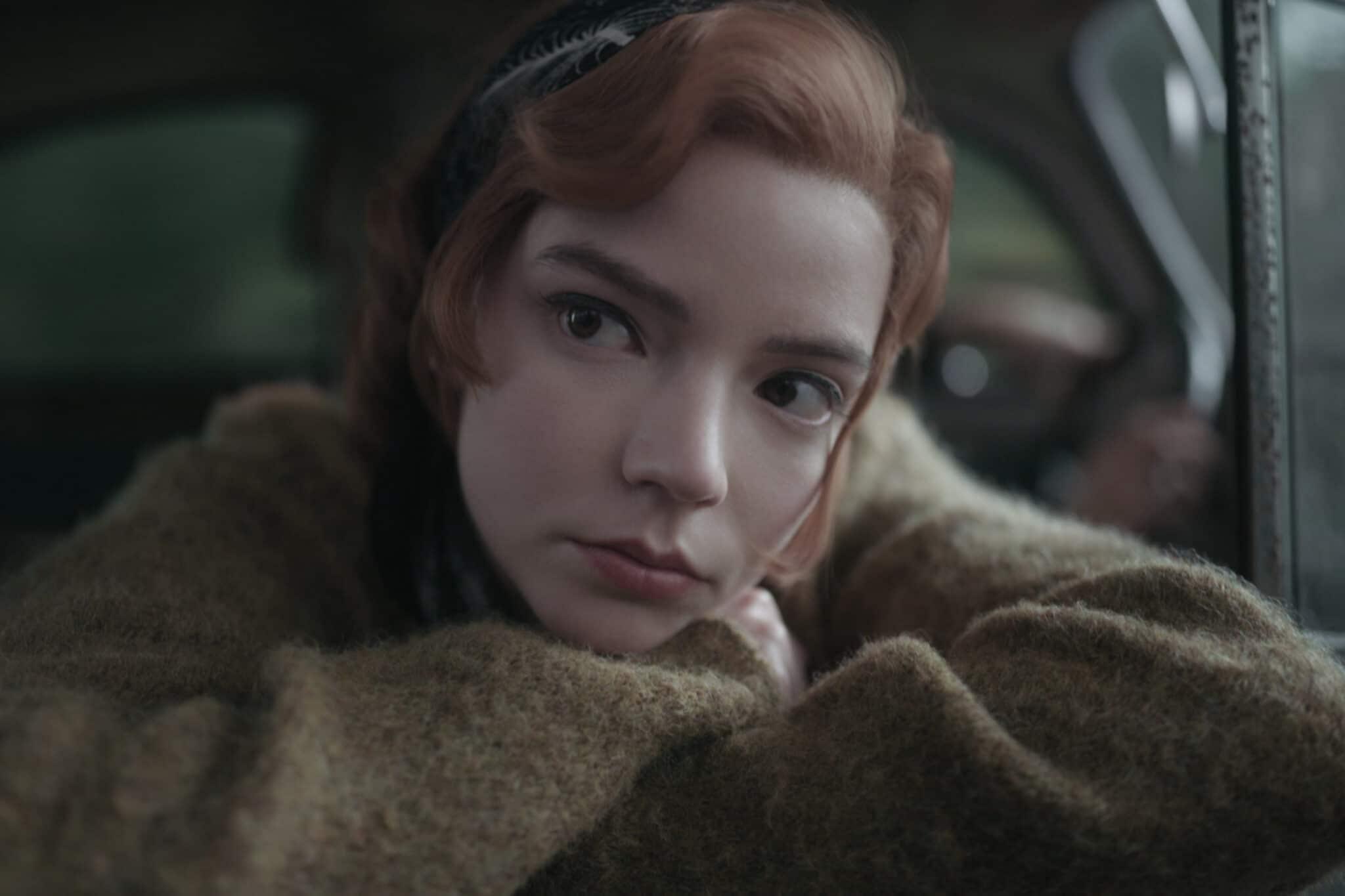 Beth (Anya Taylor-Joy) stützt ihren Kopf nachdenklich auf ihre verschränkten Arme. Sie trägt ein braunes Oberteil und einen Reif im Haar.
