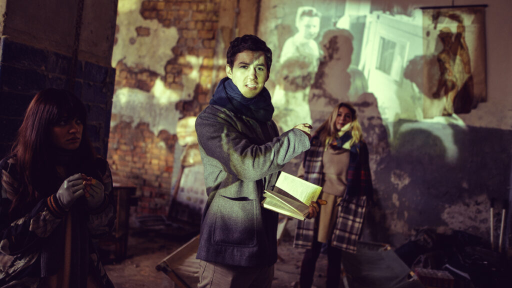 Tim-Oliver Schulz, Lisa-Marie Koroll und Nilam Farooq stehen in dem alten Krankenhaus und projezieren Filmaufnahmen auf die verfallenen Wände - Neu auf Netflix im März 2021