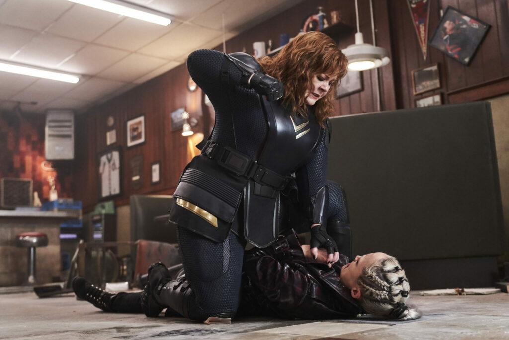Das Bild zeigt Lydia, die in Thunder Force gegen Pom Klementieff kämpft. Dabei ist McCarthy über Klementieff gebeugt und holt mit der Rechten aus.