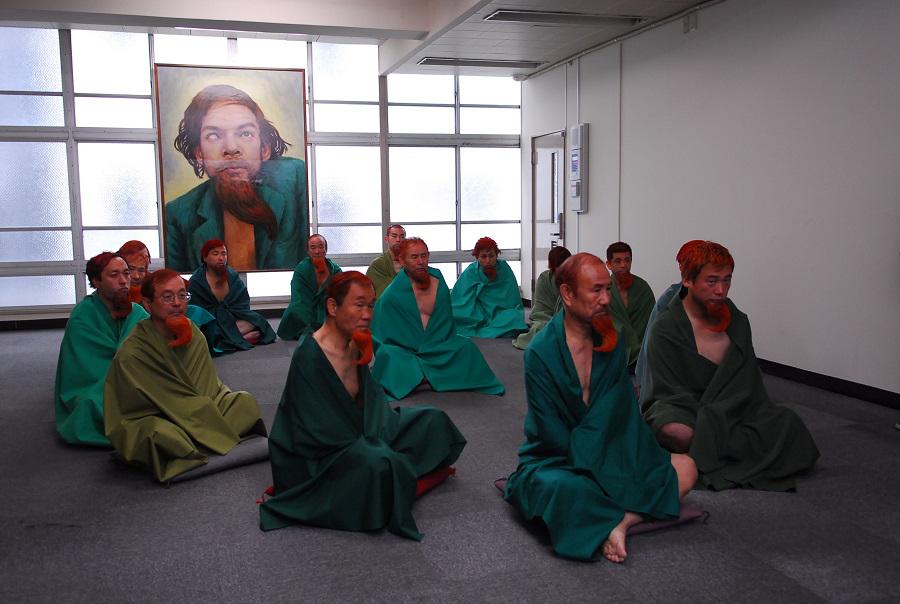 Mehrere Japaner im Schneidersitz kleiden sich wie das Kanal-Phantom (Denis Lavant) aus Tokio! Von dem hängt im Hintergrund ein Bild, das ihn fast wie einen Heiligen erscheinen lässt.