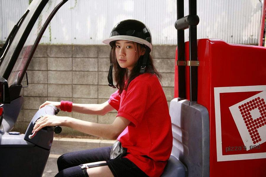 Die Pizzalieferantin (Yu Aoi), in die sich unser namensloser Protagonist aus der letzten Episode von Tokio! verliebt, sitzt in ihrem offenen Lieferwagen und guckt in die Kamera.