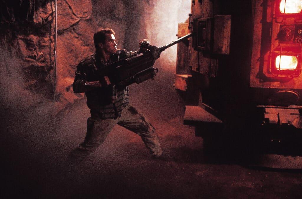 In Total Recall ist Arnie in seinem Element. Auf dem Bild steht er offenbar in einer Art unterirdischen Höhle. Dort attackiert er mit einem Bohrer ein größeres Fahrzeug.