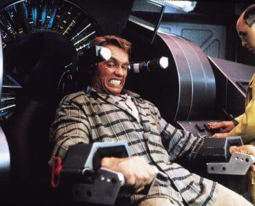 Douglas Quaid (Arnold Schwarzenegger) kämpft in Total Recall um seine Erinnerungen. Auf dem Bild sitzt Quaid gefesselt an einer Maschine. Sein Blick verrät, dass es schmerzhaft sein muss, oder zumindest gegen seinen Willen, denn er beisst sich sichtbar auf die Zähne. Zu seiner Linken steht noch ein Mann mit Halbglatze und Brille in einem gelben Kittel, der die Maschine scheinbar bedient.