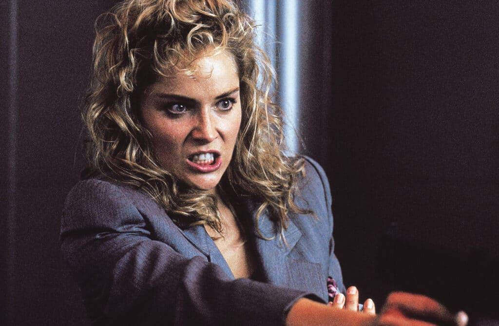 Sharon Stone spielt in Total Recall Lori, die Ehefrau von Hauptfigur Quaid. Auf dem Bild richtet sie ihren Blick mit äußerst aggressiven Zügen auf jemanden, während sie wenig erkennbar auf dem Bild eine Waffe in der rechten Hand hält.