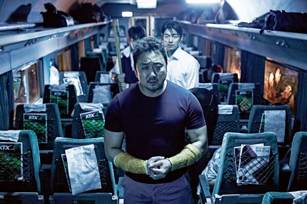 Auf dem Bild stehen Ma Dong-seok, Gong Yoo und Choi Woo-sik. Die drei Männer machen sich bereit, um in ein anderes Abteil zu gehen. Ma Dong-seok hat seine Hände gefallen. Seine Unterarme sind mit Kleber eingehüllt, wie eine Armpanzerung. Hinter ihm stehen Gong Yoo und Choi Woo-sik. Letzter hält einen Baseballschlager.