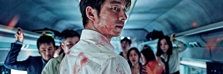 Gong Yoo spielt in Train to Busan den Fondsmanager Seok-woo. Dieser steht auf diesem Bild mit dem Rücken zum Betrachter und dreht seinen Kopf und den Oberkörper zur rechten Seite. Sein weißes Hemd weist mehrere Blutflecken auf. Im Hintergrund stehen noch mehrere Menschen.