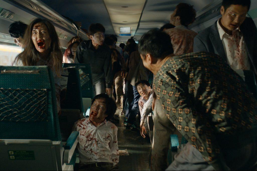 Auf dem Bild ist eines der Zugabteile zu sehen, welches voller Zombies ist. Mindestens zwanzig Zombies sind hier zu sehen, unter anderem sieht links zwischen den Sitzen einen weiblichen Zombie, der wild mit aufgerissenen und blutverschmierten Mund scheinbar faucht. Die Horde lauert nur darauf, dass neue Opfer kommen.