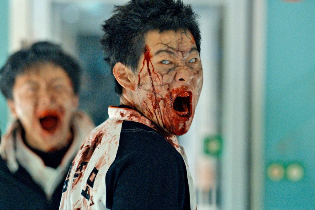 Die Zombies in Train to Busan sehen sehr erschreckend aus. Das Zombie auf diesem Bild hat die Augenfarbe komplett verblichen und das Gesicht ist, besonders um die weit aufgerissene Mundpartie, blutverschmiert.