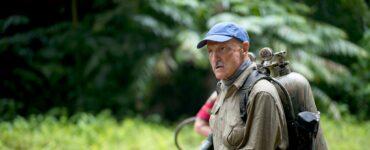 Michael Gross steht in Tremors: Shrieker Island als Graboiden-Experte Burt Gummer mit selbstgebautem Waffenrucksack vor der grünen Landschaft