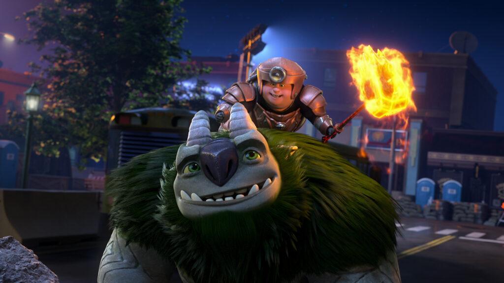 Auf dem Bild sind Tobi und Aaarrrgghh!!! zu sehen, die sich zum Kampf bereit machen. Tobi trägt eine bronzene Rüstung und hält in der linken Hand einen riesigen Hammer, der von Feuer umgeben ist. Währenddessen sitzt er auf dem Rücken von Troll Aaarrrgghh!!!, der nach oben zu Tobi blickt und diesen anlächelt. - Trolljäger - Das Erwachen der Titanen