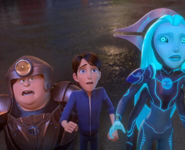 Auf dem Bild sind die Helden Tobi, Jim und Aja zu sehen, die verängstigt auf etwas oberhalb von ihnen blicken. Tobi trägt eine bronzene Rüstung samt Helm, Jim ist ohne Rüstung und nur in Alltagskleidung zu sehen und die blaue Außerirdische Aja trägt die gewohnte Uniform ihres Volkes und eine besondere Art von Krone - Trolljäger - Das Erwachen der Titanen