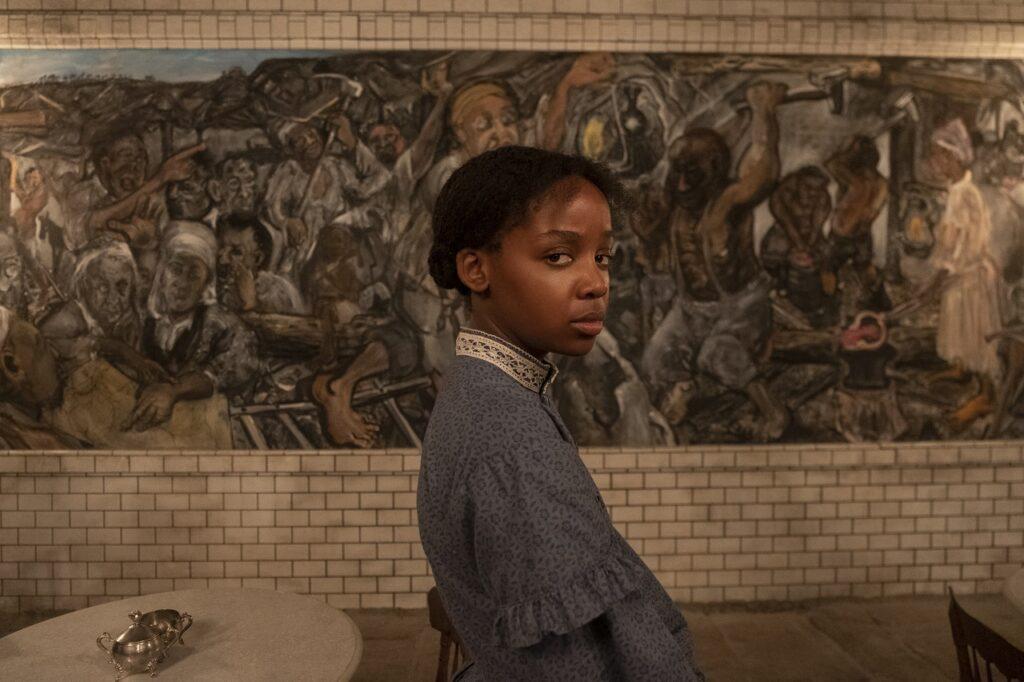 Thuso Mbedu steht bedrückt vor einem Wandgemälde, das gefangene Afro-Amerikaner bei der schweren Sklavenarbeit darstellt - Neu bei Prime im Mai 2021