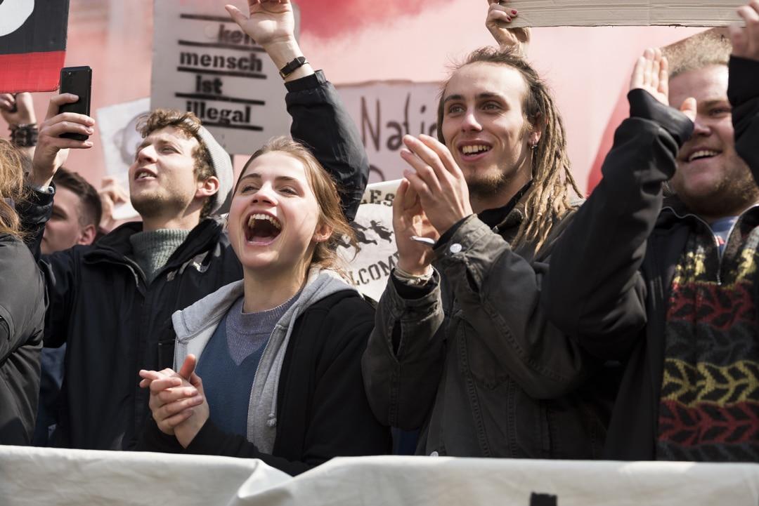 Antifa-Demonstranten demonstrieren klatschend und gröhlend mit Spruchbannern