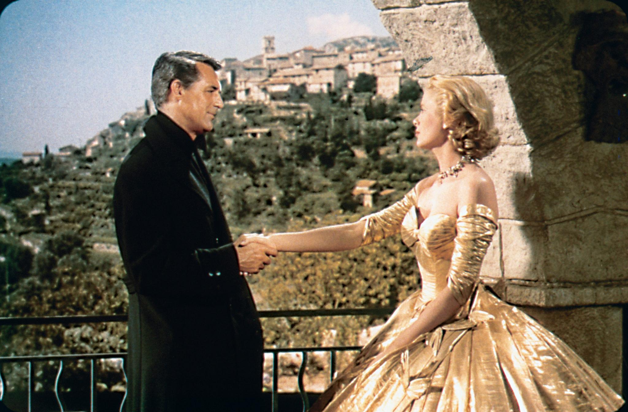 John Robie (Cary Grant) in schwarzem Mantel und Frances (Grace Kelly) in goldenem Kleid schütteln sich in Über den Dächern von Nizza die Hand. Im Hintergrund ist ein Dorf an der Küste der französischen Riviera zu sehen.