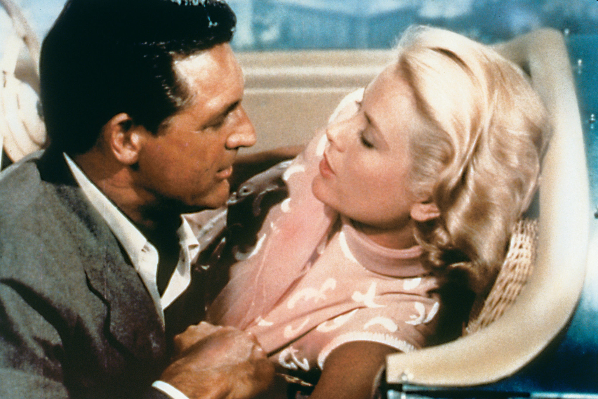 John Robie (Cary Grant) und Frances (Grace Kelly) sitzen in Über den Dächern von Nizza in einem Cabriolet und sind kurz davor, sich zu küssen.