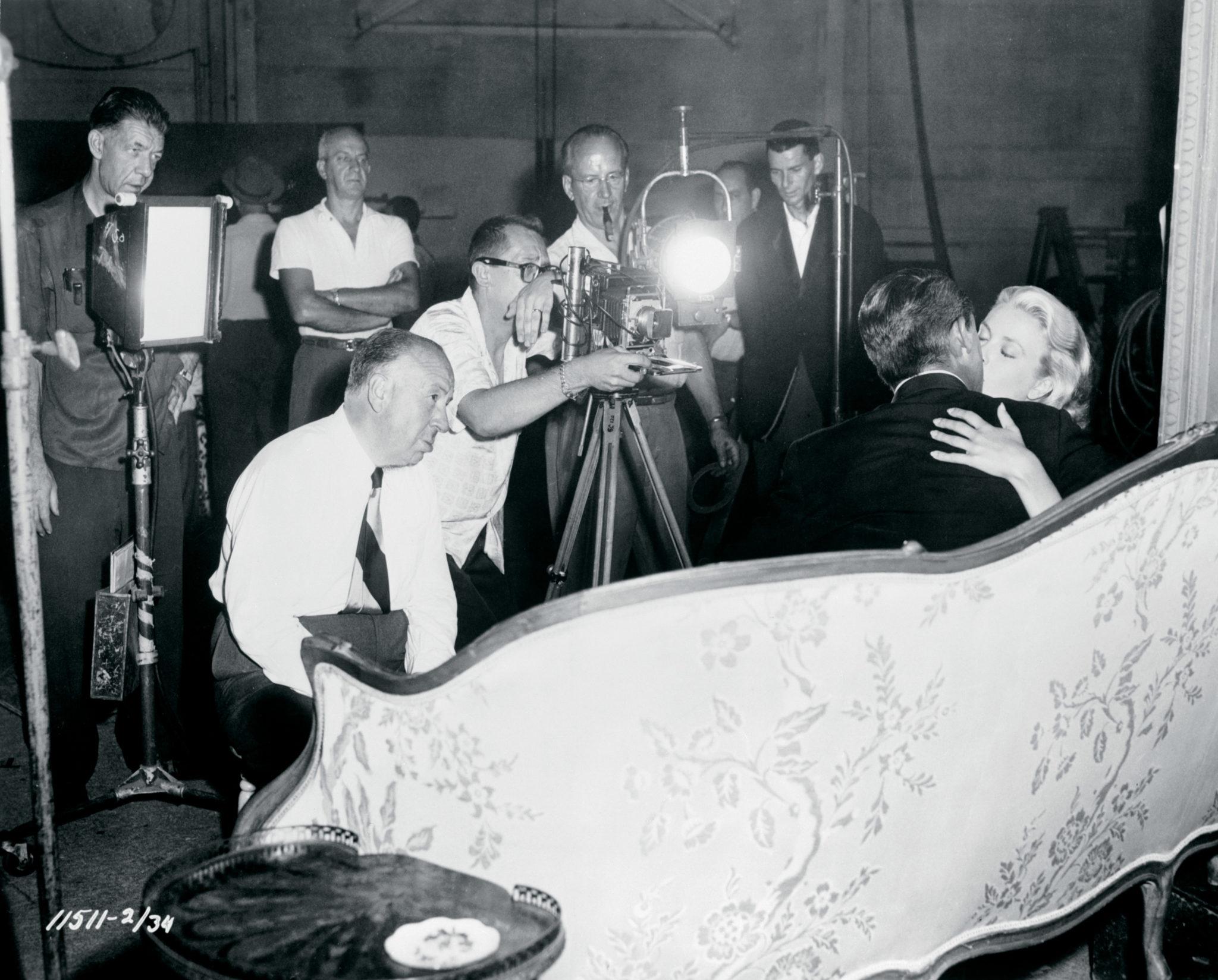 In einem schwarzweißen Behind-the-Scenes-Foto von Über den Dächern von Nizza sehen wir Regisseur Alfred Hitchcock und Kameramann Robert Burks zusammen mit weiteren Crew-Mitgliedern beim Dreh der Kuss-Szene zwischen Cary Grant und Kelly Grace im Hotel Carlton.