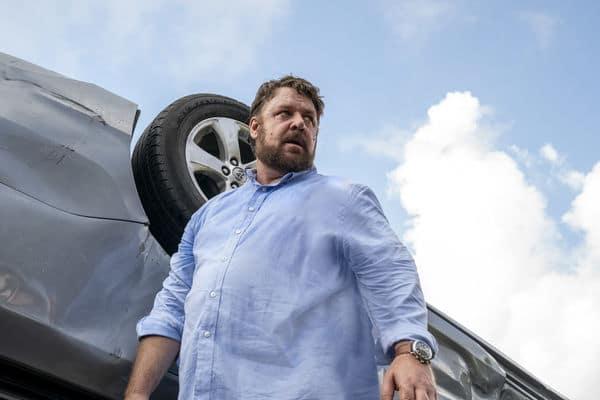 """Mit einigen Kilos auf den Rippen geht Russell Crowe bis zum Äußersten in """"Unhinged - Ausser Kontrolle"""". Auf dem Bild filmt die Kamera von unten nach oben, was Crowe noch größer und übermächtiger erscheinen lässt. Hinter ihm steht ein Auto auf dem Kopf. Er richtet seinen Blick in die Ferne."""