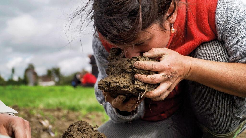 Eine Frau riecht an einer Bodenprobe, die sie in den Händen hält.