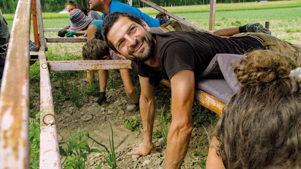 Biobauern rupfen Wildkräuter vom Acker. Um ihr Gewicht besser zu verteilen, liegen sie nebeneinander auf einer Planke, die von einem Trecker über das Feld geschoben wird.