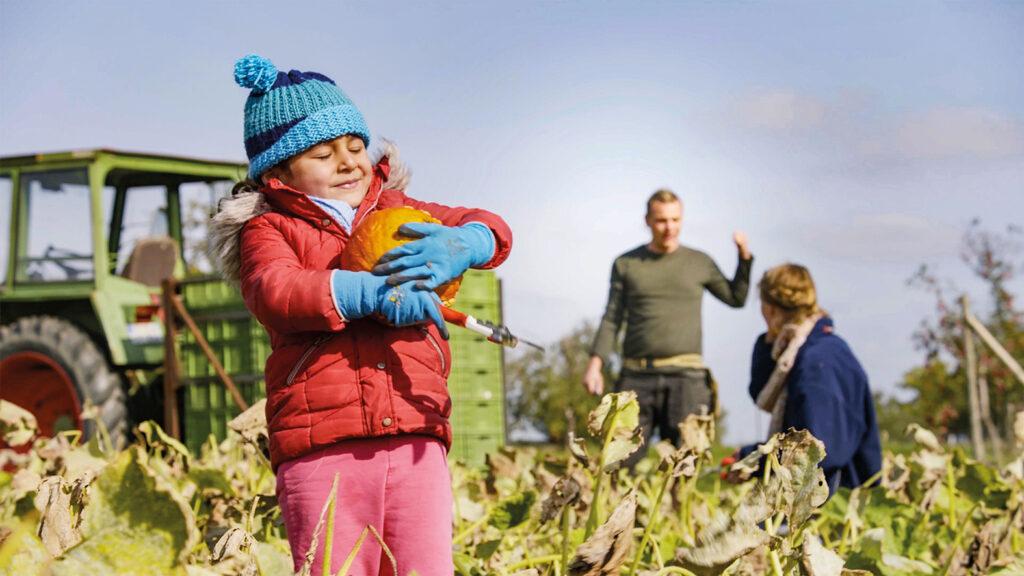 Ein Kind hält in Unser Boden, unser Erbe einen frisch geernteten Kürbis in der Hand, während die Eltern im Hintergrund bei der Feldarbeit sind.