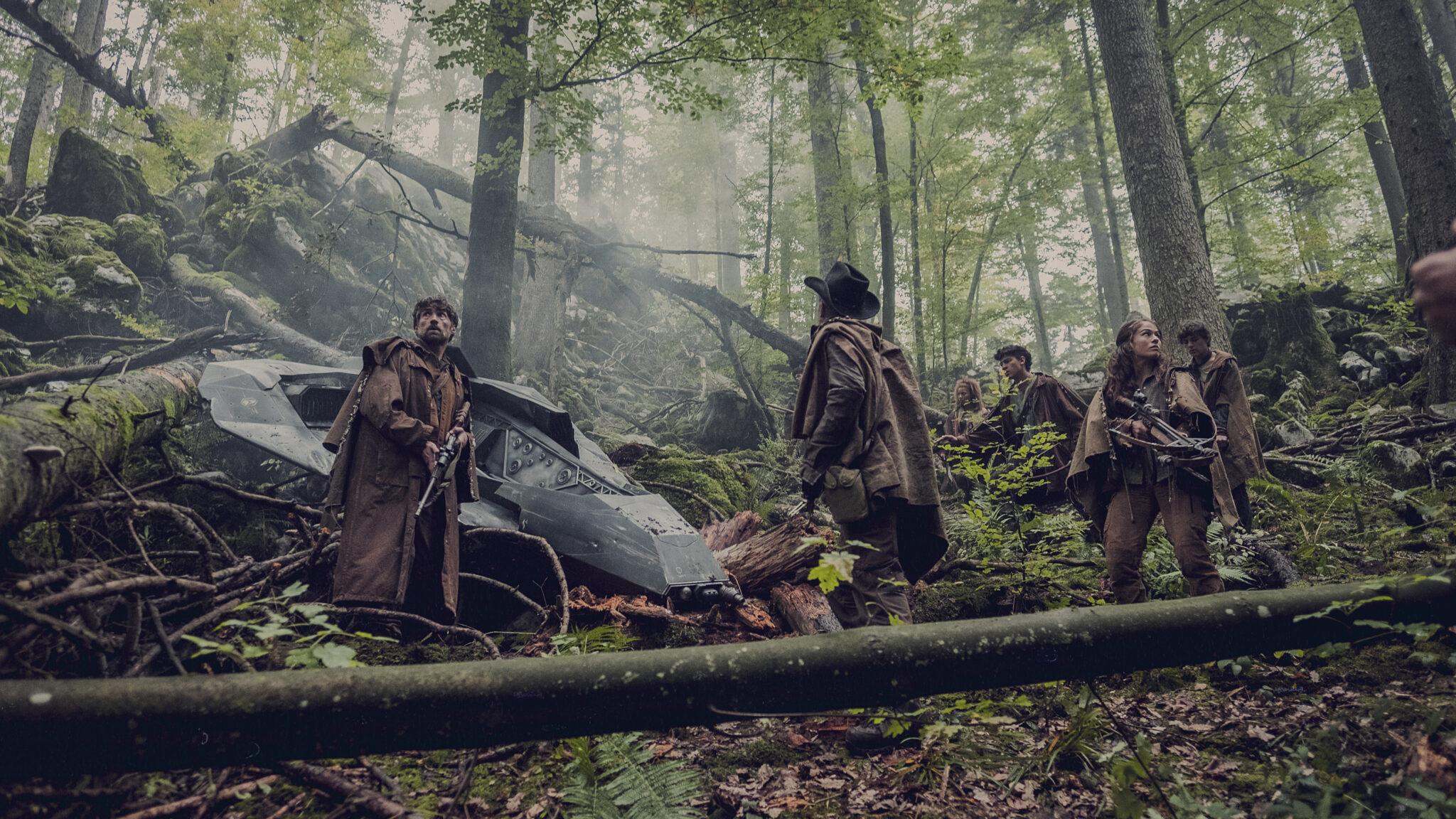 Man sieht fünf Personen in brauner Kleidung in einem Wald, die ein abgestürztes Flugobjekt in Augenschein nehmen.