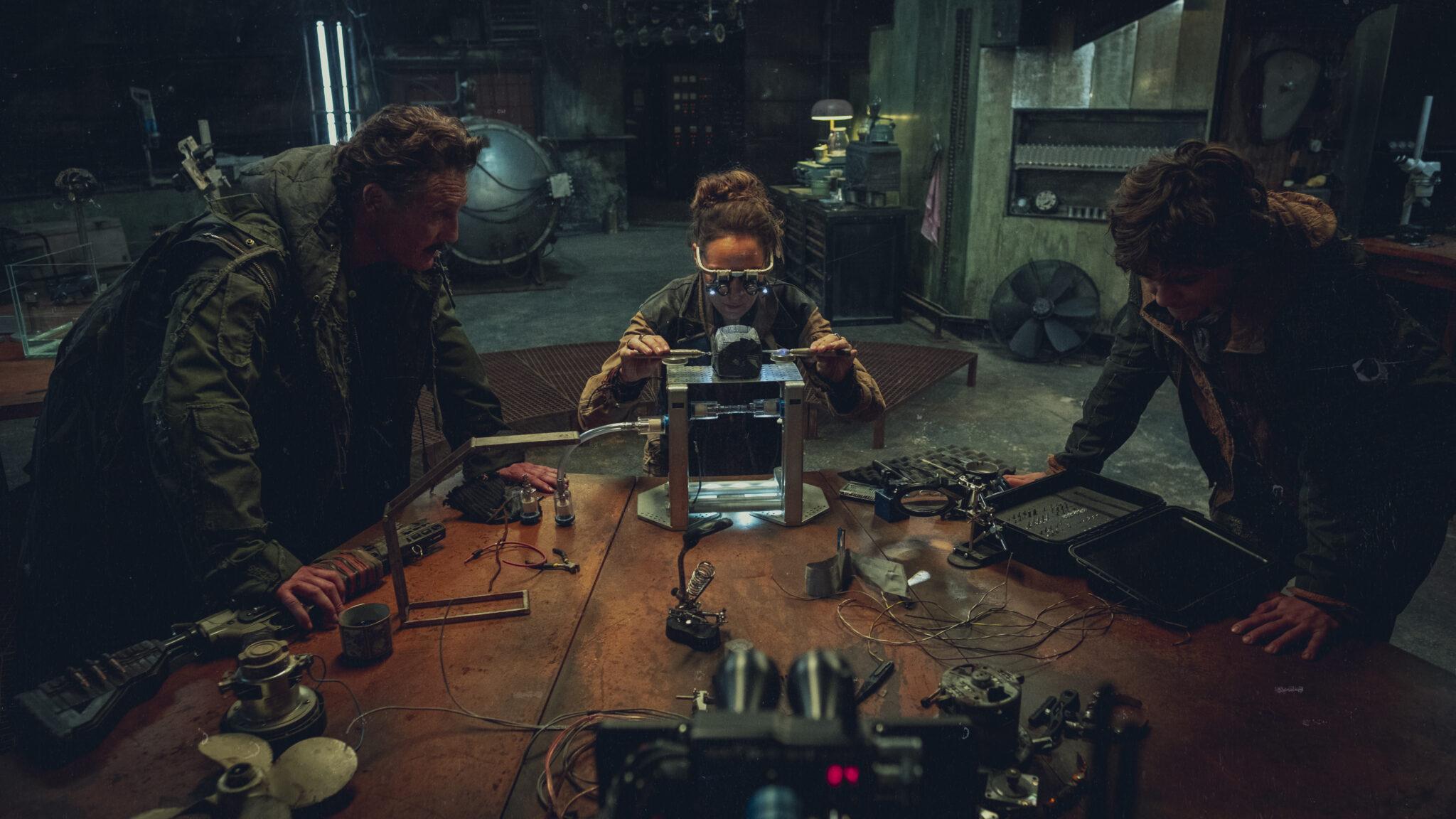 Drei Personen um einen Tisch herum: auf dem Tisch liegen zahlreiche Apparate, Bauteile und Drähte. Die Frau in der Mitte hat eine Art Brille auf und untersucht einen leuchtenden Gegenstand. Die beiden Männer, rechts und links im Bild, stützen sich auf den Tisch und blicken auch auf das leuchtende Objekt in Tribes of Europa.