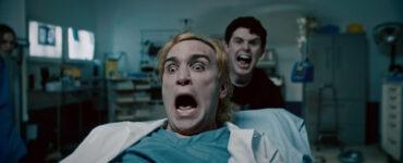 Ari Millen liegt auf dem Krankenbett, Evan Marsh schiebt ihn, beide schreien - Vicious Fun