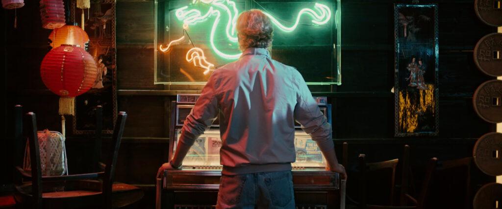 Ari Millen steht mit dem Rücken zum Zuschauer an die Jukebox gelehnt, darüber ein Neonbild mit einem Drachen - Vicious Fun