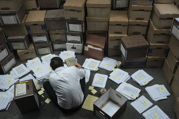 """In dieser Szene von """"Vergiftete Wahrheit"""" kämpft sich Rob Bilott (Mark Ruffalo) durch mehrere Kisten mit Akten. Diese Kisten sind um ihn herum aufgestapelt. Die Akten, die er bereits aus diesen geholt hat, türmt er vor sich, so dass er kaum Platz zum Bewegen hat."""