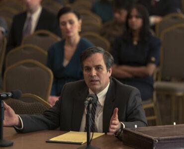 """In dieser Szenen von """"Vergiftete Wahrheit"""" ist Mark Ruffalo als Rob Bilott zu sehen, der an einem Tisch vor Gericht sitzt. Er redet in ein Mikrofon und gestikuliert mich geöffneten Armen und Handflächen. Vor ihm liegen gelbe Blätter und links davon eine Aktentasche."""