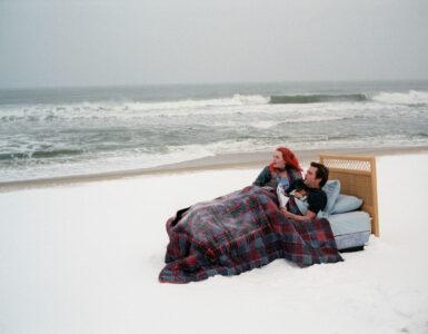 """""""Vergiss mein nicht"""" ist ein Beispiel dafür, dass der deutsche Filmtitel sich enorm vom Originaltitel unterscheidet. Auf dem Bild sind Kate Winselt und Jim Carrey zu sehen, die zugedeckt in einem Bett liegen. Dieses Bett befindet sich an einem weißen Strand direkt am Wasser. Die beiden Schauspieler blicken aufs Meer hinaus."""