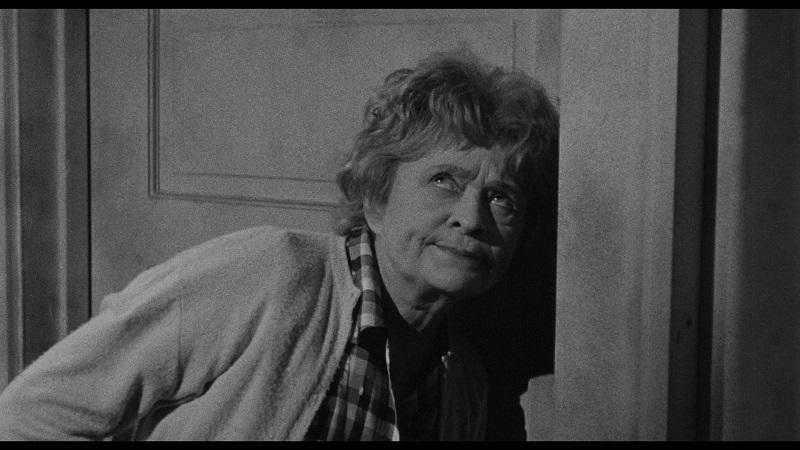 Die Hauswirtin lauscht angespannt an Walters Tür und verdreht die Augen in Das Vermächtnis des Prof. Bondi