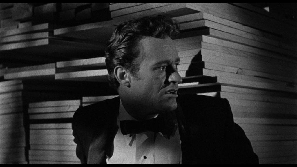 Der herausgeputzte Walter versteckt sich hinter einem Regal voller Bretter in Erwartung seines nächsten Opfers in Das Vermächtnis des Prof. Bondi