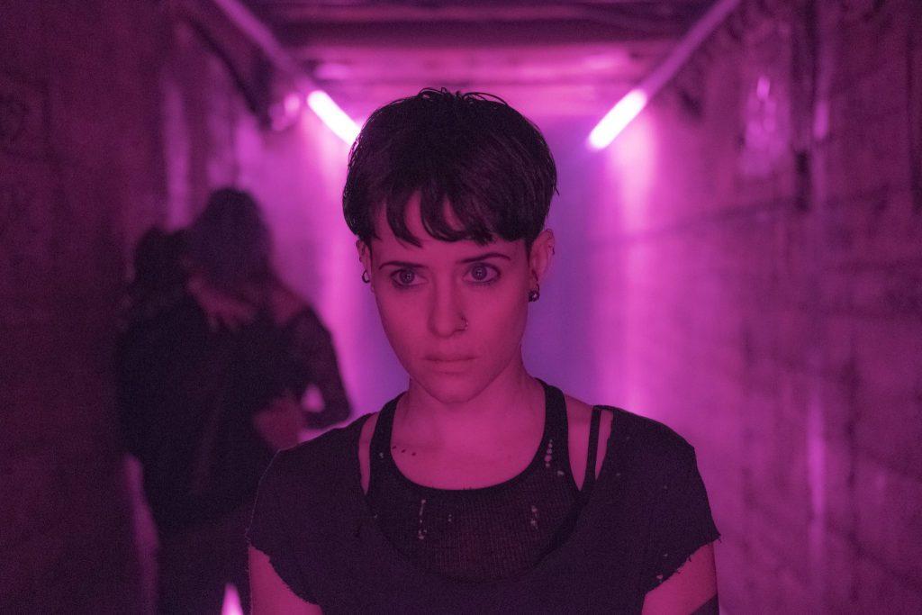 Lisbeth geht einen in lilanen Neonlicht beleuchteten Gang entlang, während im Hintergrund ein Pärchen an der schmutzigen Wand herummacht - Neu auf Netflix im November 2020