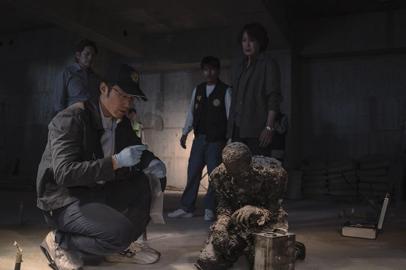 Ein Ermittler hockt vor einer verbrannten Leiche, seine Kollegen schauen im Hintergrund interessiert drein - Neu auf Netflix im April 2020
