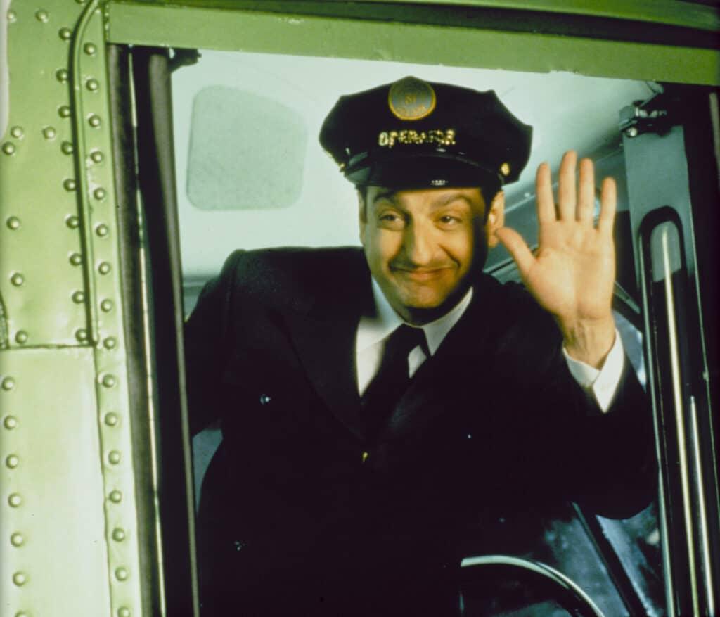"""David Paymer spielt den Busfahrenden Fährmann in """"Vier himmlische Freunde"""". Auf dem Bild sieht man ihn in einer typisch amerikanischen Busfahrerkluft. Zu dieser gehört ein weißes Hemd mit dunkler Krawatte. Darüber eine dunkle einfarbige Jacke und eine ebenfalls dunkle Mütze, die wie eine klassische Polizisten Kopfbedeckung aussieht. Paymer lächelt auf dem Bild und hebt seine linke Hand zum Gruß."""