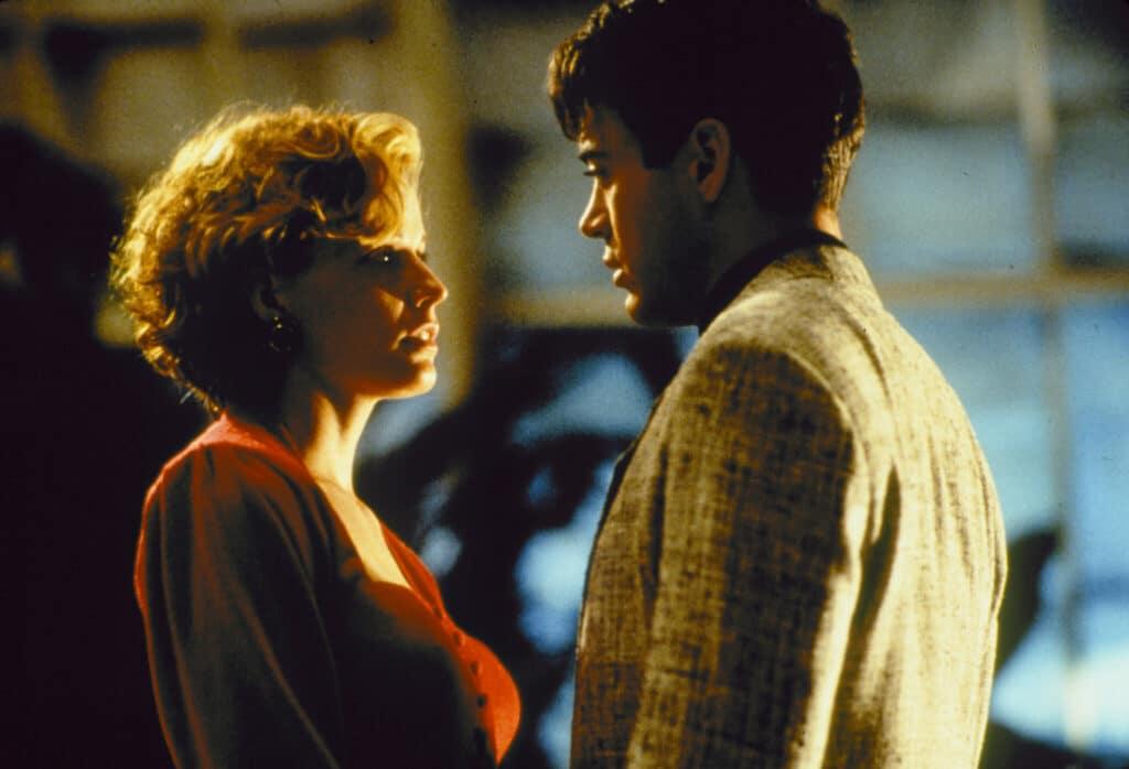 """Anne (Elizabeth Shue) und Thomas (Robert Downey Jr.) in einem innigen Moment in """"Vier himmlische Freunde"""". Beide schauen sich tief in die Augen. Die Lichtverhältnisse sind abgedunkelt, wodurch viele Schatten auf die beiden Gesichter fallen. Shue trägt ein rotes Kleid und Downey Jr. ein beige-graues Jacket."""