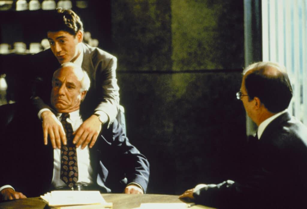 """Robert Downey Jr. spielt wörtlich wie besessen in """"Vier himmlische Freunde"""". Auch auf dem Bild ist er nicht in Besitz seines Körpers. Dieser wurde von einem der weiblichen Geister übernommen. Dies ist zu erkennen, da Downey Jr. typische weiblichen Manierismen zeigt und auf dem Bild einen älteren Mann im Anzug bezirzt, der an einem Besprrechungstisch sitzt. Dafür steht er hinter ihm und legt seine Arme über die Schultern des älteren Herren. Darüber hinaus blickt er mit Schmollmund und großen Augen in die Runde."""