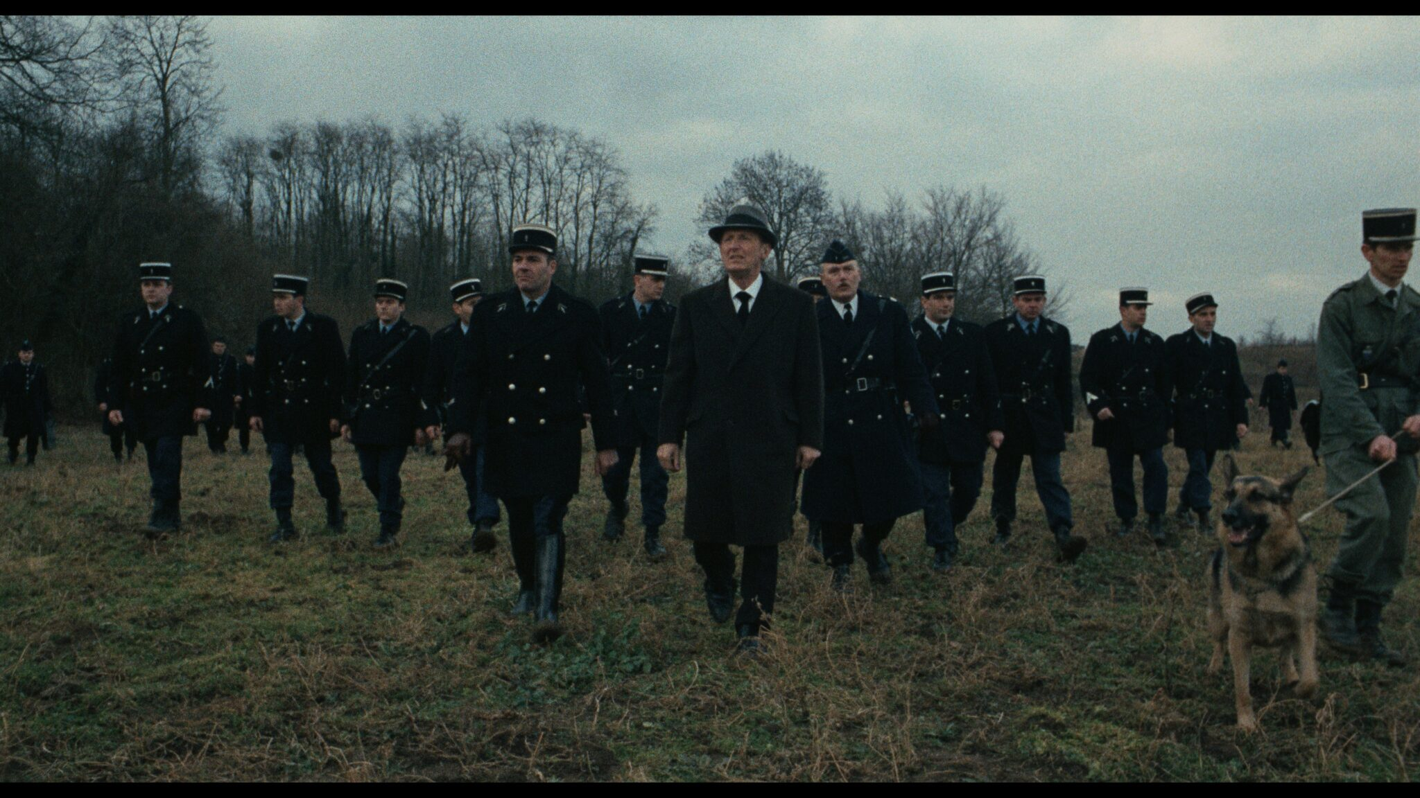 """Mattei (André Bourvil) und dutzende weitere Polizisten suchen in """"Vier im roten Kreis"""" in einer Reihe laufend nach dem flüchtigen Vogel (Gian Maria Volonté). Auch Polizeihunde werden eingesetzt, um die Spur aufzunehmen."""