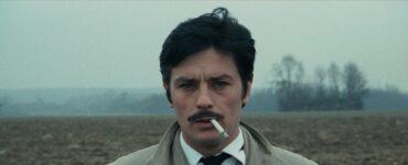 """Corey (Alain Delon) steht in """"Vier im roten Kreis"""" in hell-beigem Trenchcoat und schwarzer Krawatte auf einem verlassenen Feld und starrt angestrengt in die Kamera. Die Zigarette liegt lässig im Mundwinkel."""